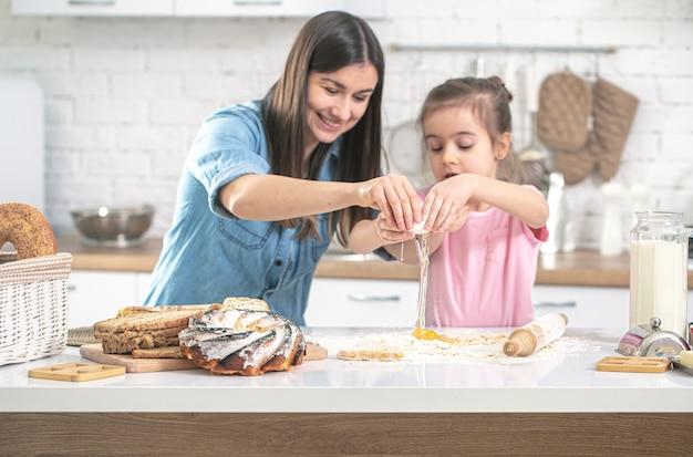 幸せな家族。ママと娘はキッチンでペストリーを準備します。愛する家族と家族の価値観の概念。健康的な家庭料理。