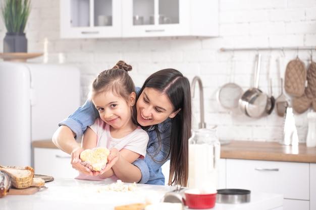 幸せな家族。ママと娘はキッチンでペストリーを準備します。