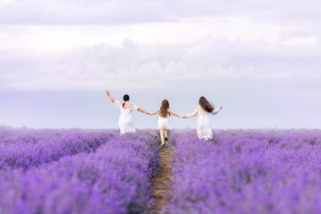 Счастливая семья, мама и дочери бегут через лавандовое поле. вид со спины. счастливая семья в поле лаванды.