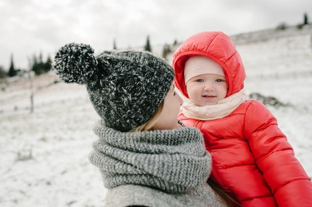 행복한 가족 : 엄마와 소녀는 눈 덮인 겨울에 재미 있고 놀고 있으며 산, 자연을 산책합니다. 여행을 즐기는 어머니와 어린이 딸. 서리 겨울.