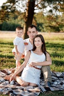 幸せな家族のお母さんお父さんと赤ちゃんの息子が夏の晴れた日に一緒に時間を過ごす自然で幸せ。