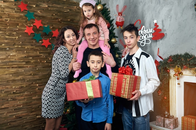 Счастливая семья: мама, папа и трое детей у камина на зимние каникулы. сочельник и новый год.