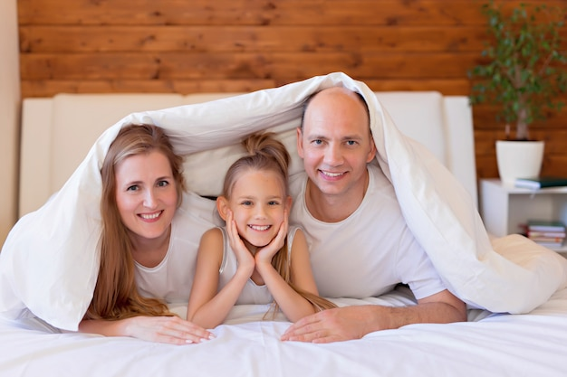 Happy family, mom, dad and daughter in bed at home in the bedroom under the covers