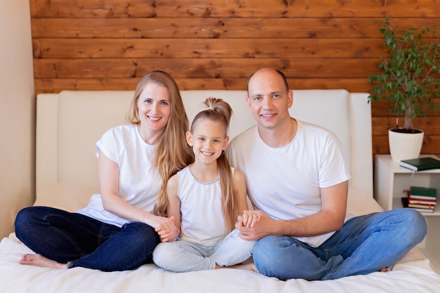 Happy family, mom, dad and daughter in bed at home in the bedroom