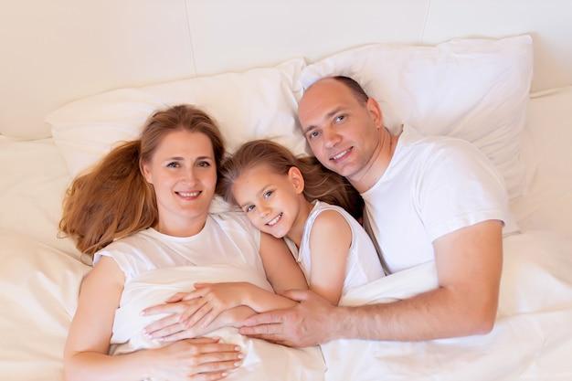 幸せな家族、ママ、パパ、娘が自宅の寝室のベッドで寝る