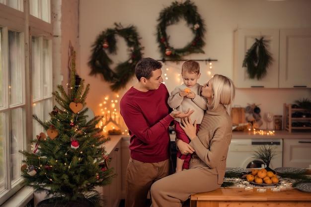 幸せな家族のお母さん、お父さんの息子は、自宅のキッチンで新年の準備をしています。