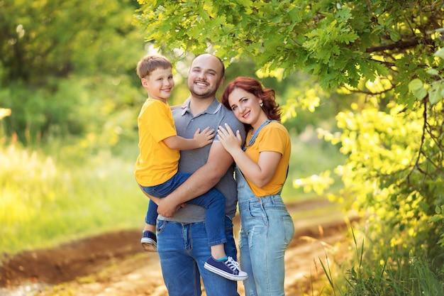 Счастливая семья, мама, папа, сын гуляют, обнимаются летом на свежем воздухе.