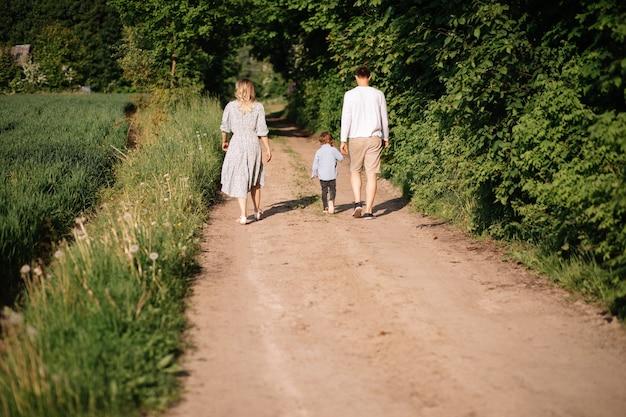 행복한 가족 엄마, 아빠, 아들이 즐겁게 시골길을 걷고, 손을 잡고, 후면 사진 프리미엄 사진