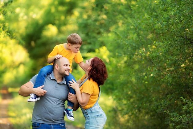Счастливая семья, мама, папа, сын гуляют, обнимаются, целуют друг друга на улице летом