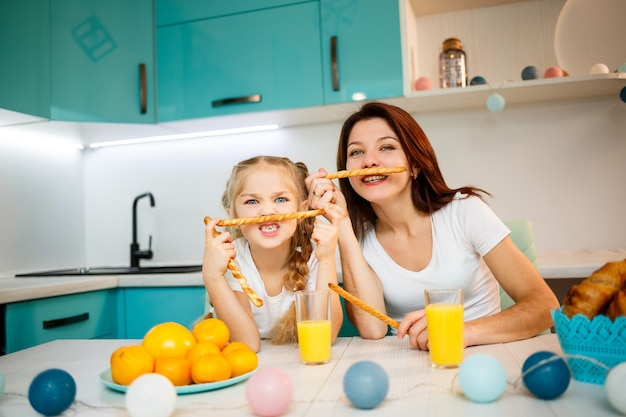 Happy family, mom and daughter are sitting in the kitchen and eating bread sticks. family relations of the child with the parents