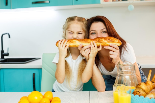 Happy family, mom and daughter eat one bread biting from different sides. family relations of the child with the parents