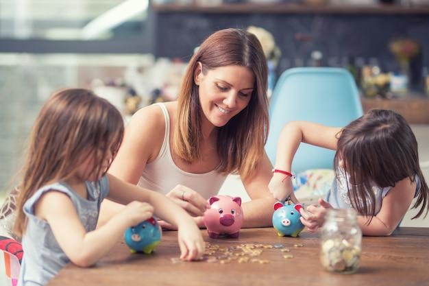행복한 가족 엄마 딸은 돈 돼지 저금통 미래 투자 저축을 저장합니다.
