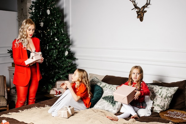 幸せな家族のお母さんは、自宅のクリスマスの装飾が施された部屋で娘たちにギフトボックスを贈ります。