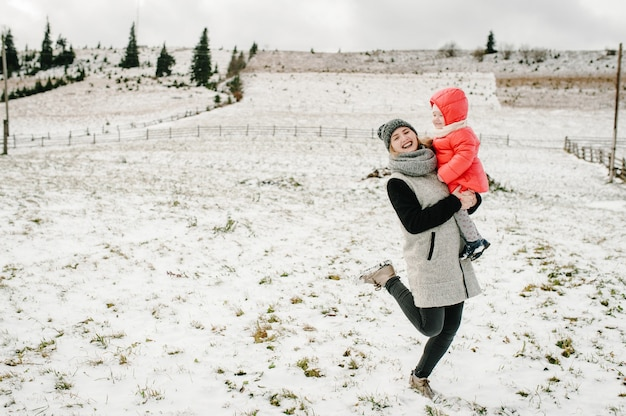 Happy family mom hugs girl and having fun and playing on snowy winter, walk in mountain.