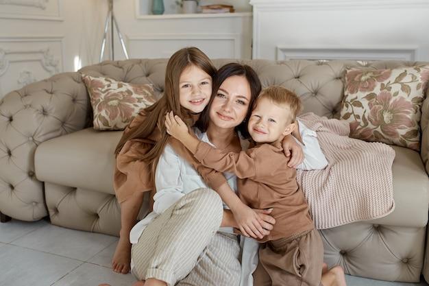 幸せな家族。ママは息子と娘を抱きしめます、愛。女性、男の子、女の子の顔に陽気な楽しい感情。家族のレジャー