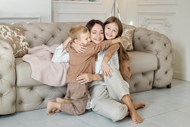 행복한 가족. 엄마는 아들과 딸을 안아줍니다. 여자, 소년 및 소녀의 얼굴에 밝고 즐거운 감정