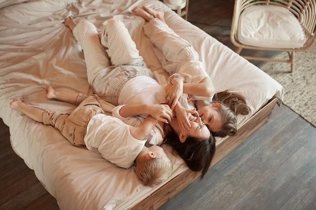 Счастливая семья. мама обнимает сына и дочь