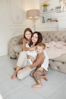 幸せな家族。ママは息子と娘を抱きしめます