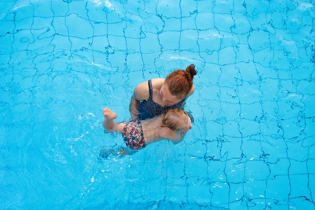 Happy family mom teaches her daughter  years old to swim in the pool top view