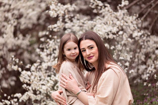 Happy family, mom with a daughter on a background of flowering trees.