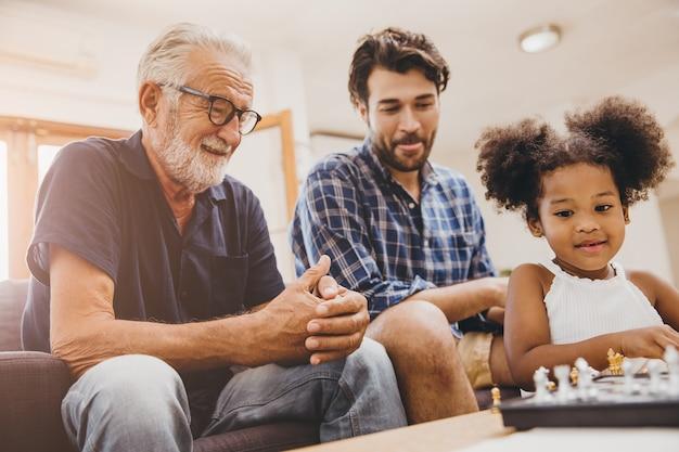 チェスゲームをしている家で幸せな瞬間の子供と小さな女の子と息子との幸せな家族の瞬間の長老。
