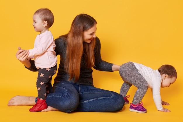 Счастливая семья, мамочка с очаровательными и милыми девочками-близняшками