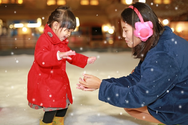 Happy family mother and adorable little girl has a fun in snow, winter time.