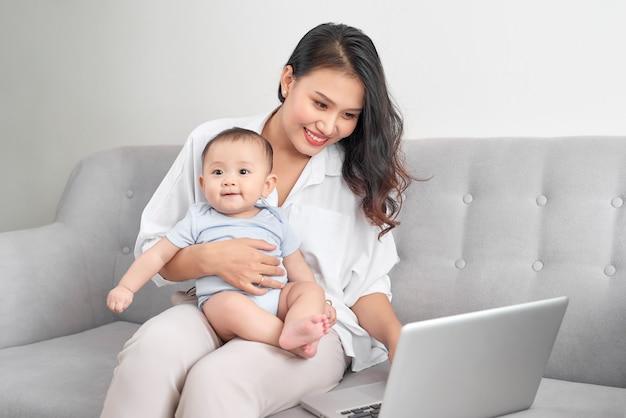 Счастливая семья, мать и ребенок дома, используя портативный компьютер