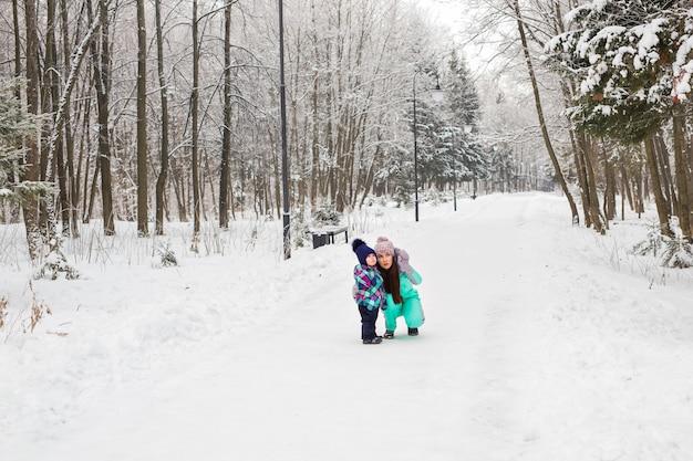Счастливая семья, мать и дочь девочки, играя и смеясь над зимой на открытом воздухе в снегу.