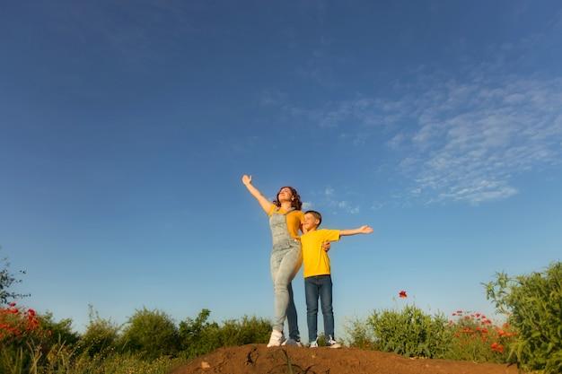 Счастливая семья, мать и маленький сын летом на природе на закате