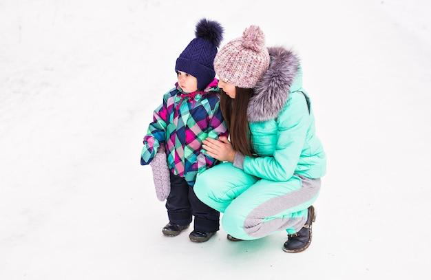 Счастливая семья, мать и дитя на зимней прогулке в лесу