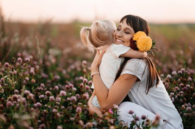 幸せな家族、母と子の娘は日没時に夏の自然の中で花の牧草地を抱いています