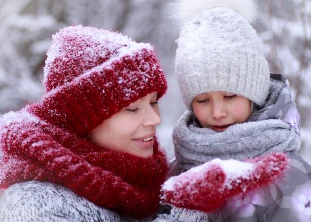 Счастливая семья матери и дочери ребенка весело, играя на зимней прогулке на открытом воздухе.