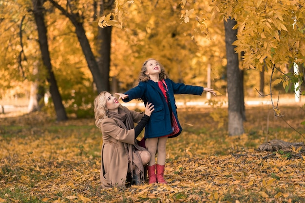 秋の散歩に幸せな家族の母と子の娘