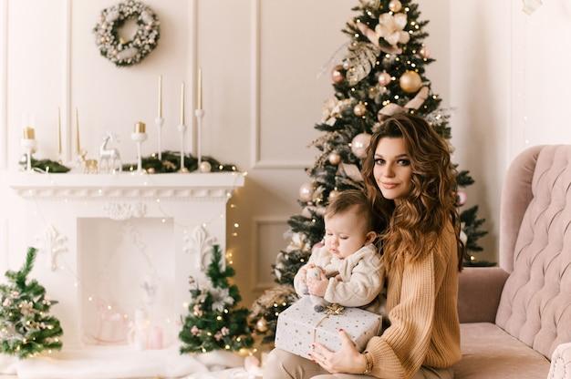 贈り物とクリスマスツリーでクリスマスの朝に幸せな家族の母と子の娘