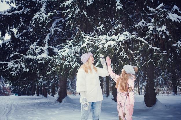 Счастливая семья. мать и дитя девочка на зимней прогулке на природе.