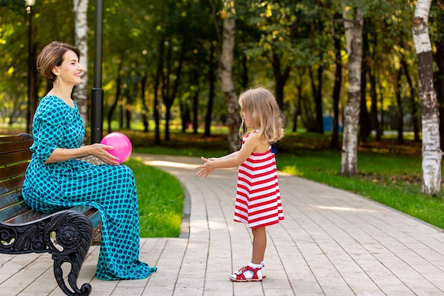 Счастливая семья, мать и дитя маленькая дочь играют с воздушным шаром и гуляя в парке и наслаждаясь красивой природой.