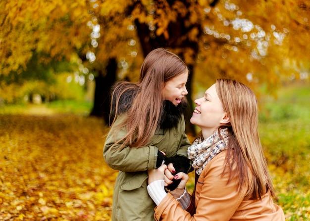 幸せな家族の母と子の小さな娘が秋の散歩で遊んでいます。幸せな家族。学校の休暇。