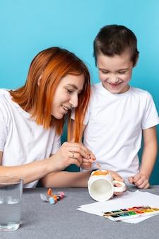 Счастливая семья, мать и ребенок вместе рисуют дома на синем фоне. детское творчество.
