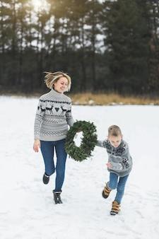 Счастливая семья, мать и ребенок, сын в джинсах и вязанных свитерах, бегают и веселятся