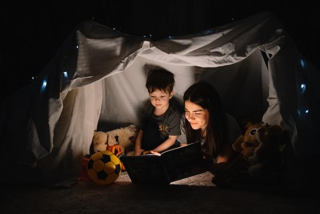 집에서 텐트에서 손전등과 함께 책을 읽고 행복 한 가족 어머니와 자식 아들. 가족 개념 프리미엄 사진