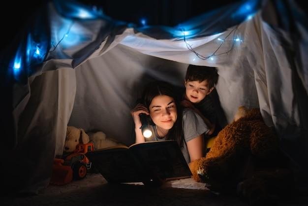 집에서 텐트에서 손전등과 함께 책을 읽고 행복 한 가족 어머니와 자식 아들. 가족 개념