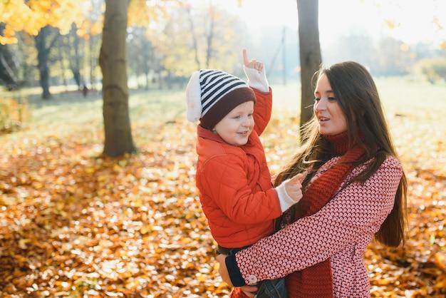 Счастливая семья, мать и дети на осенней прогулке в парке