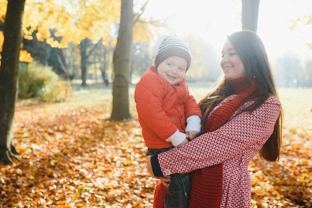 幸せな家族の母と秋の公園で散歩