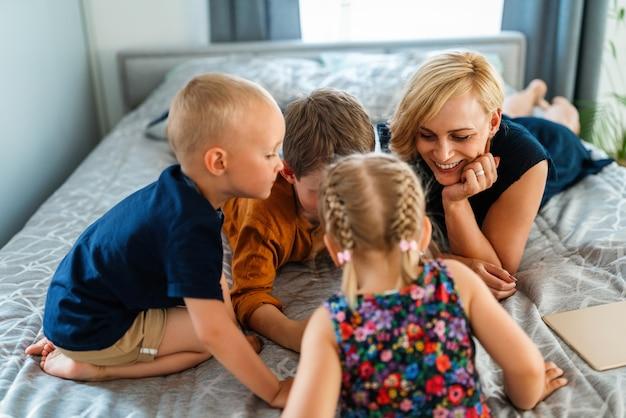 행복한 가족 어머니와 아이들이 집에서 디지털 기기를 가지고 노는 것입니다. 기술, 아이 개념입니다.
