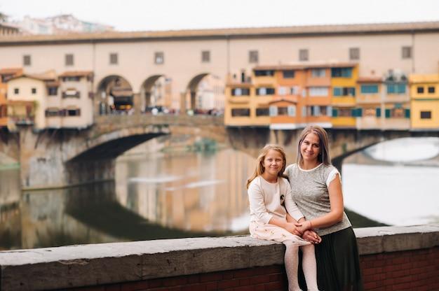 フィレンツェのヴェッキオ橋を背景に幸せな家族の母と娘。イタリアの家族の散歩。トスカーナ。