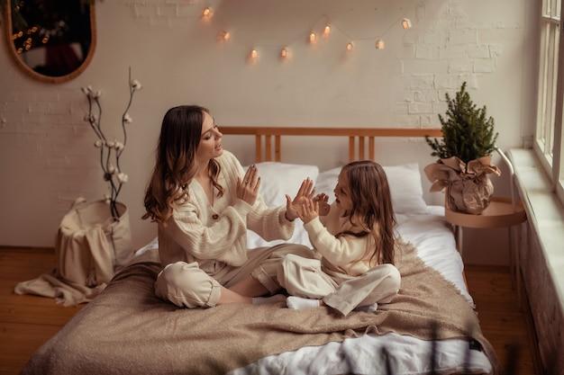 幸せな家族の母と娘はベッドで家で楽しんでいます