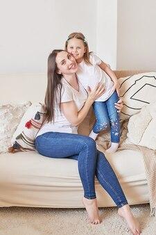 Счастливая семья. мать и дочь дома. молодая женщина и девушка. день матери и ребенка. доброе утро и концепция любви. светлый домашний интерьер.