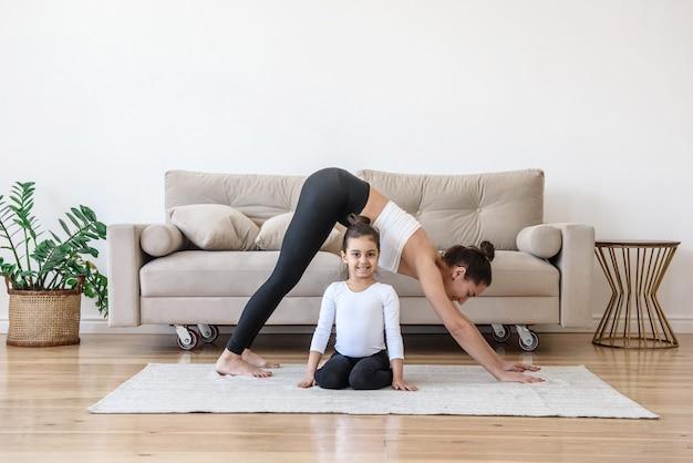 Счастливая семья, мать и дочь вместе занимаются спортивной йогой дома