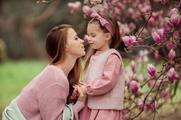 Счастливая семья. мать и дочь на прогулке весной под розовым деревом магнолии держатся за руки и нежно смотрят в глаза